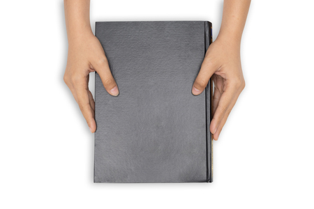Hands holding closed book with black blank cover on white background.