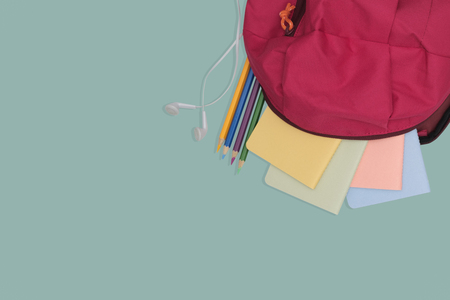 school bag with book and color pencil isolated on green background, back to school concept.