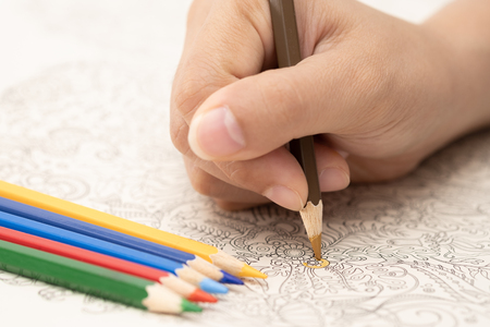 Female hand with colorful pencil is painting on doodle book.