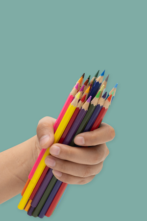 Hands holding a bunch of pencils on a green background. Stock Photo