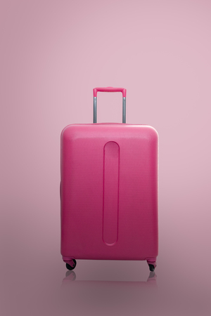 Traveler pink suitcase or cabin size luggage on pink background with shadow, Journey and travel concept. Reklamní fotografie