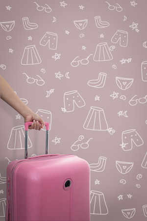 Hand holding traveler pink suitcase or cabin size luggage with hand drawn clothes and icons on pink background with copy space, travel concept. Reklamní fotografie