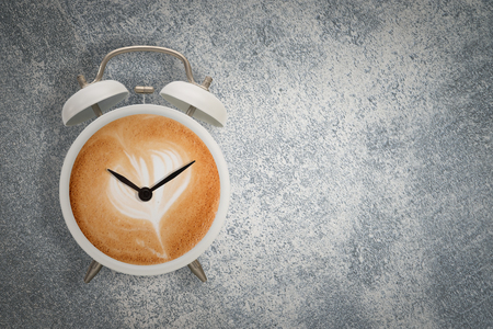 Hot coffee with frothy foam in white alarm clock design is coffee time concept. Reklamní fotografie