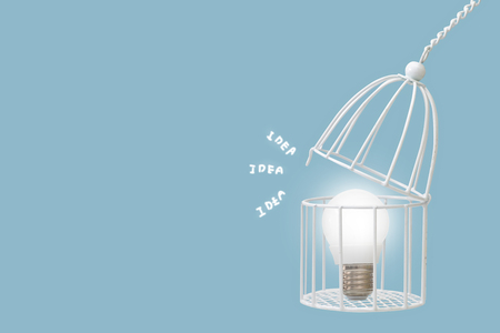 Lamp bulb in bird cage isolated on blue background, minimal idea concept.