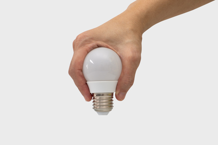 Hand holding a light bulb shape isolated on white background.
