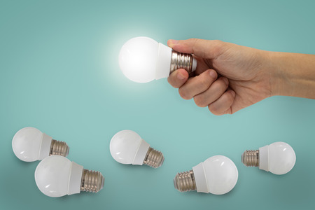 Hand holding illuminated light bulb, idea, inspiration concept.