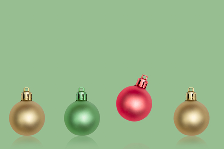 red and green christmas ball Ornaments on green background. minimal christmas concept. Reklamní fotografie