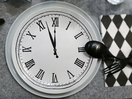 Dish with clock, black fork and spoon, Eating time concept.
