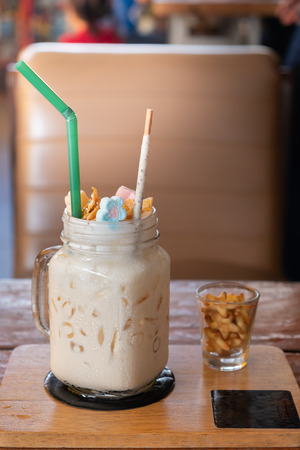 Milkshake with marshmallow, sweet  cookies, served in glass mason jar.