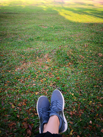 Womans legs in grey shoes sit on dry leaves in the park.