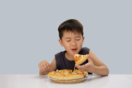 Cute boy eating pizza isolated on blue background. Reklamní fotografie