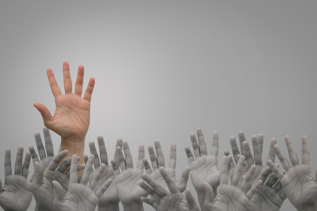 Group of human hands raised high up on grey  background. Concept Business
