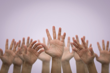Group of human hands raised high up on pink background. Concept Business