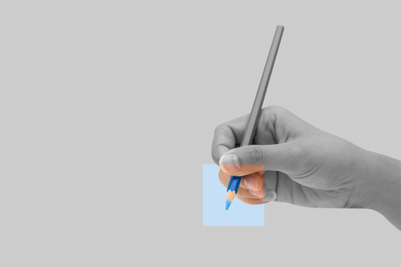 Female hand with blue color pencil isolated on grey background. Minimal idea concept.