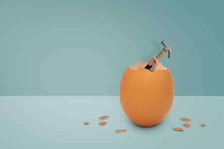 Holding the hammer out of the egg shell on blue background, easter concept.