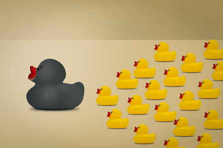 Rubber ducks in  leadership concept on a yellow background.