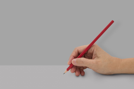 Female hand with red color pencil isolated on gray background.