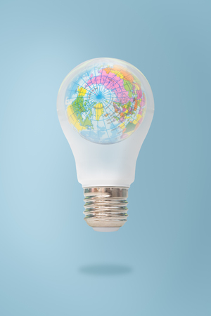 Blue world map in light bulb isolated on white background, symbolizing environmental care or green energy, Elements of this image furnished by NASA.
