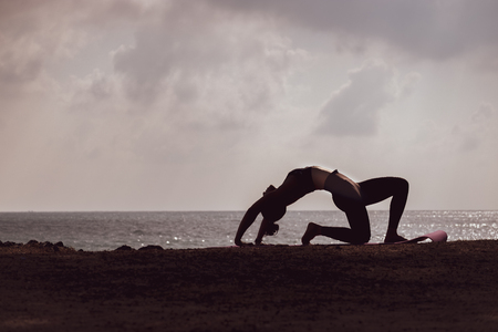 silhouette of woman practicing yoga on the beach in the morning. Фото со стока