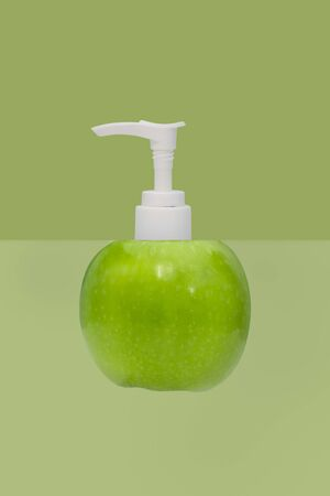 Plastic pump bottle and apple on green background.