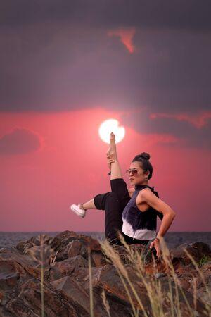 Yoga corebalance Gymnastics on the rock in pink sky. Imagens - 133377867