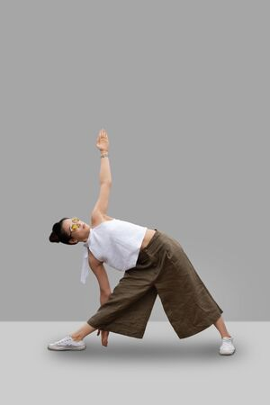 yoga female  standing in Utthita Trikonasana, Extended Triangle Pose on grey background.