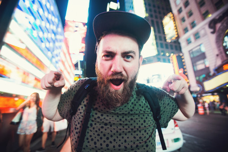 Funny bearded man posing smiling and taking selfie photo on Times Square in New York while travel across USA