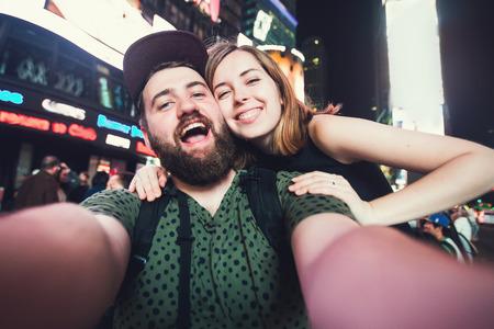 nacht: Glückliche Dating Paar in der Liebe unter selfie Foto auf dem Times Square in New York während der Reise in USA auf Hochzeitsreise