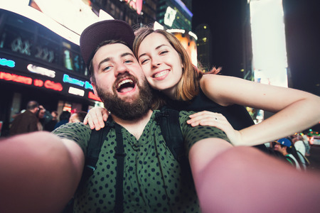 date: Happy dating couple in love taking selfie photo on Times Square in New York while travel across USA on honeymoon