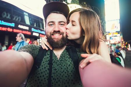 across: Happy dating couple in love taking selfie photo on Times Square in New York while travel across USA on honeymoon
