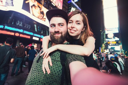 couple dating: Happy dating couple in love taking selfie photo on Times Square in New York while travel across USA on honeymoon