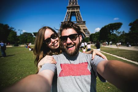 여행: 행복한 커플 키스 미소와 프랑스를 통해 여행하는 동안 파리에서 에펠 탑 앞에 selfie의 사진을 복용