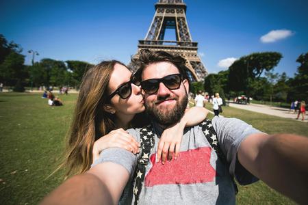 travel: Šťastný úsměv pár líbání a při selfie fotografii v přední části Eiffelova věž v Paříži, na cestách po celé Francii