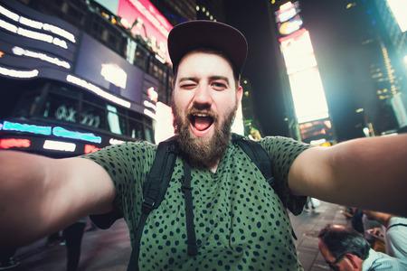 変なひげを生やした男バックパッカー笑顔と米国間で一人旅しながらニューヨークのタイムズ ・ スクエアの selfie 写真を撮る 写真素材