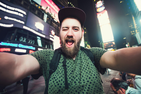 Funny bearded man backpacker smiling and taking selfie photo on Times Square in New York while travel alone across USA Stock Photo