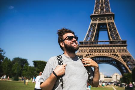niño con mochila: Feliz sonriente joven que permanece turista mochilero masculina frente a la Torre Eiffel en París, Francia.