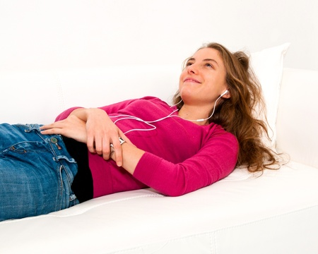 beautiful young woman enjoys listening music in headphones photo