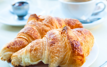 Breakfast with coffee and croissants in a basket on table Stock Photo - 9278310