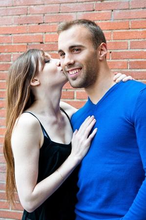 besos apasionados: Feliz retrato de joven beso pareja con pared de ladrillo rojo Foto de archivo