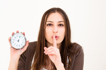 Portrait of a beautiful young woman hushing and holding alarm clock Stock Photo - 9796237