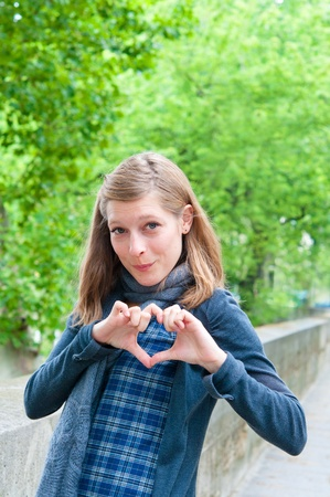 portrait young woman make heart shape by her hands  in the streets of Paris Stock Photo - 9796273