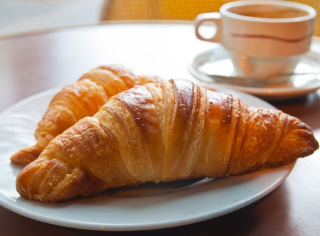 french bread rolls: Breakfast with coffee and croissants in a basket on table Stock Photo