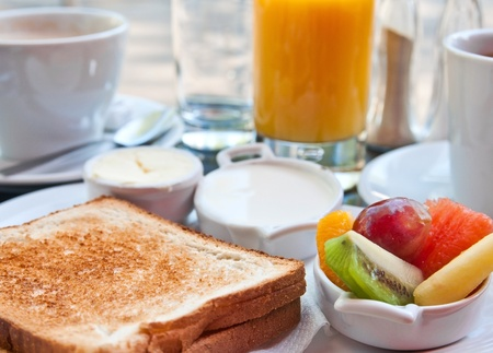 Breakfast with orange juice and fresh fruits on table photo