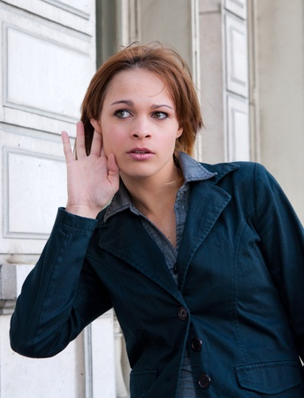 eavesdropping: Young woman relying on hand-ear listening in the streets of Paris