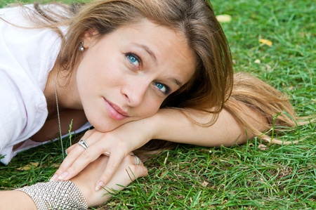 beautiful young lady enjoying free time while lying in wild nature photo