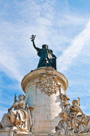 marianne: The Famous Statue of the Republic in Paris looking away in the blue sky. The Statue of the Republic was built in 1880 in the center of the place of the Republic in Paris. It symbolizes the victory of the Republic in France . Stock Photo