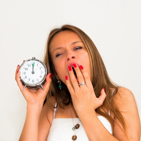 deprivation: Yawn-beautiful young woman holding alarm clock