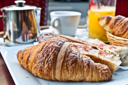 french bakery: Breakfast with coffee and croissants in a basket on table Stock Photo