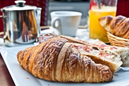 pasteleria francesa: Desayuno con caf� y croissants en una cesta sobre la mesa Foto de archivo