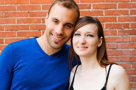 Young couple in love smiling with red brick wall photo